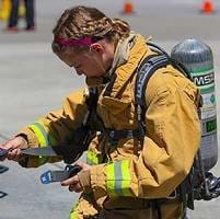 A young woman putting on fire protection gear
